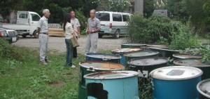 試験的に搬入された一次生成物のドラム缶の前で説明を聞くディレクター